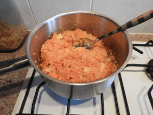 onion, carrot and rice in a pan