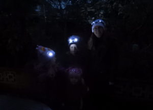 Family wearing Bright Eyes hats with eyes lit up