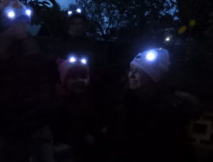 Mum and boy wearing Bright Eyes hats with eyes lit up
