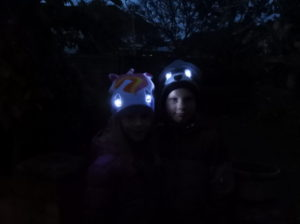 Children wearing Bright Eyes hats with eyes lit up