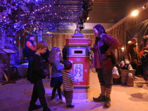 Children and elf posting letters in post box in LaplandUK Wishing Store