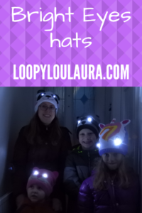Pinnable pic of Family wearing Bright Eyes hats with eyes lit up