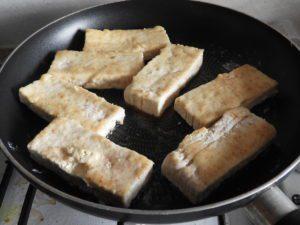tofu slices frying in pan