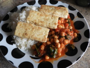 dished up plate of chickpea and spinach curry with tofu slices on top